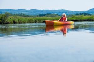 donna che si distende su un kayak e godersi la vita foto