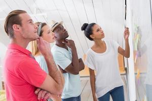 gruppo creativo che esamina le note appiccicose sulla parete foto
