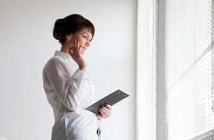 donna d'affari guarda fuori dalla finestra foto