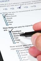 mano che regge la penna, compilando il sondaggio sull'esperienza del cliente foto