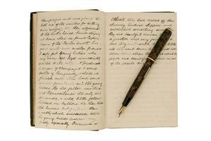 pagine in un diario di viaggio antico con penna stilografica foto