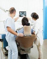 dentisti che discutono con il paziente foto
