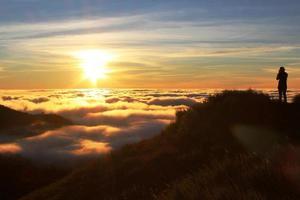 uomo che cattura foto del tramonto dorato