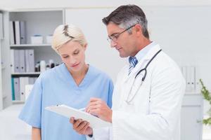 medico e infermiere che discutono sopra le note sulla lavagna per appunti foto