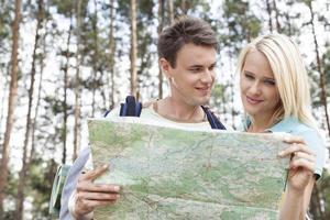 giovani viaggiatori con zaino e sacco a pelo felici che leggono mappa in foresta foto