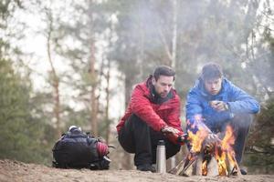escursionisti maschi che si scaldano le mani al fuoco nella foresta