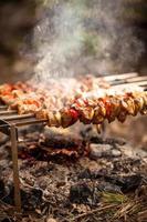 spiedino di carne cotta sul fuoco foto