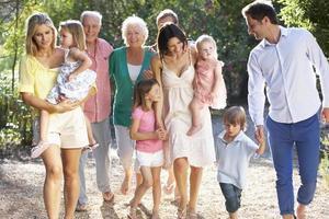 tre generazioni di una famiglia in campagna camminano insieme