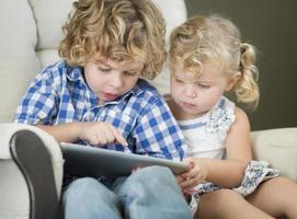 giovane fratello e sorella che utilizzano insieme il tablet del computer