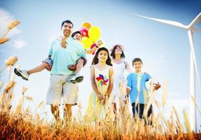 famiglia che gioca all'aperto concetto del campo dei bambini foto