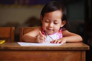 bambino che scrive e sorride foto