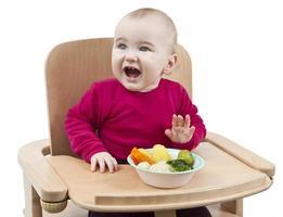 bambino che mangia nel seggiolone foto