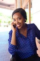 donna sorridente di affari che per mezzo del telefono cellulare foto