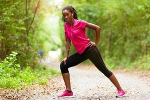 allungamento del pareggiatore della donna dell'afroamericano - forma fisica, la gente e foto