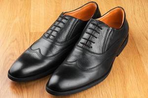 le classiche scarpe da uomo stanno sul pavimento di legno foto
