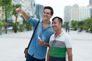 i turisti di due uomini sorridono il giro turistico del dito del punto, corsa asiatica della miscela foto