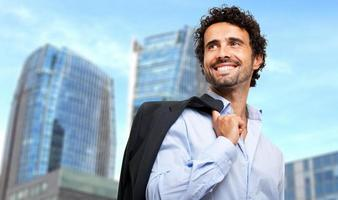 uomo d'affari sorridente che tiene la sua giacca all'aperto foto