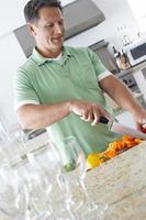 uomo tritare peperoni al bancone della cucina foto