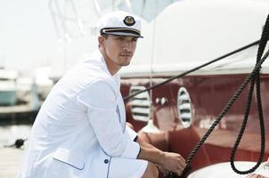 capitano che tiene la corda dello yacht foto