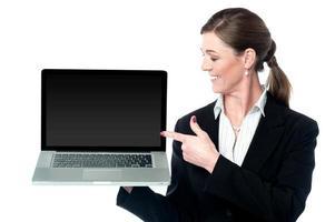 dirigente di vendita femminile che presenta nuovo computer portatile foto
