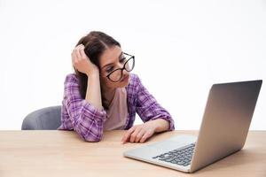 studentessa stanca che si siede con il computer portatile foto
