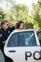 agente di polizia grezzo arrestando autista femmina foto
