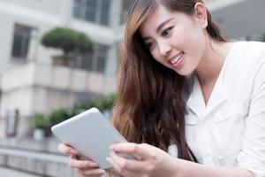 studentessa asiatica che utilizza compressa nel campus foto