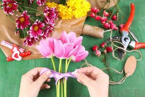 mani femminili che compongono bellissimo bouquet, primo piano foto