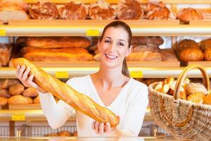 panettiere femminile nel suo forno con baguette foto