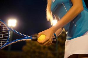 tennis femminile che tiene racchetta e palla foto