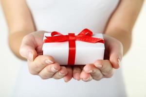 mani femminili che tengono il contenitore di regalo foto