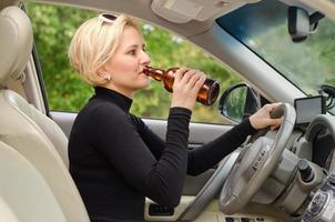 giovane driver femminile che beve e che guida foto