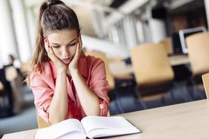 studentessa che studia in biblioteca foto