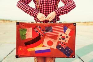 la donna tiene la valigia con bandiere di francobolli foto