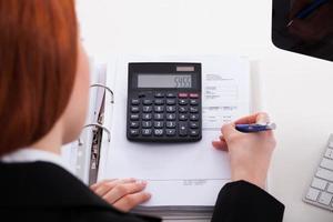 donna di affari che per mezzo del calcolatore alla scrivania foto