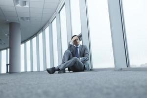 uomo d'affari seduto sul pavimento foto