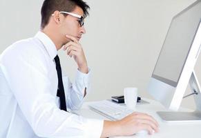 uomo d'affari giovane lavora in ufficio moderno sul computer foto