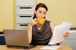 donna di affari che mangia tè mentre esaminando i documenti in ufficio foto