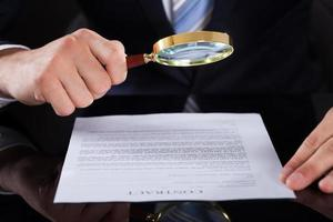 carta di contratto d'esame dell'uomo d'affari con la lente d'ingrandimento foto