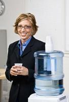 donna di affari che sta al dispositivo di raffreddamento di acqua foto