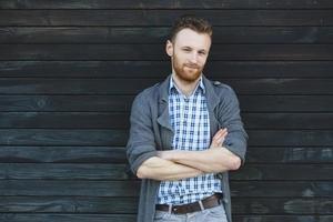Ritratto di giovane uomo alla moda contro la parete di legno foto