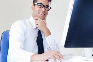 felice l'uomo d'affari giovane lavora in ufficio moderno sul computer foto