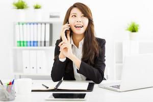 donna felice di affari che parla al telefono in ufficio foto