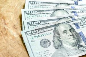 una pila di cento banconote in dollari primo piano su fondo di legno. foto