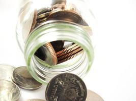 risparmio di denaro, monete da versare, soldi baht thailandesi nel bicchiere foto