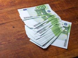 primo piano di 100 banconote in euro su sfondo di legno. foto