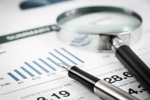 lente d'ingrandimento e penna sul grafico su table.accounting foto