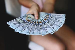 mani della donna che tengono soldi foto