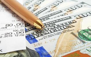 concetto di business - buono denaro, penna e contanti foto