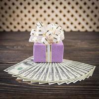 dollari e confezione regalo su fondo in legno foto